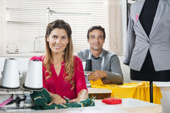 Confident Tailors Sitting At Workbenches In Factory. Portrait of confident male and female tailors sitting at workbenches in sewing factory Royalty Free Stock Photography