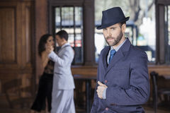 Confident Tango Dancer Standing While Partners Performing In Res. Portrait of confident male tango dancer standing while partners performing in restaurant Stock Image