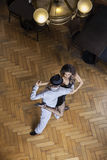 Confident Tango Dancers Performing On Hardwood Floor. High angle view of confident male and female tango dancers performing on hardwood floor at restaurant Royalty Free Stock Image