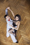 Confident Tango Partners Smiling While Performing In Restaurant. High angle portrait of confident male and female tango partners smiling while performing in Royalty Free Stock Photo