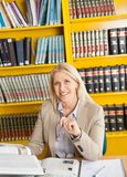 Confident Teacher With Books Sitting At Table In Stock Images