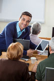 Confident Teacher Showing Digital Tablet To Senior Students In C. Portrait of confident teacher showing digital tablet to senior students at desk in computer Stock Photo