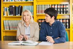 Confident Teacher With Student Looking At Her In. Portrait of confident teacher with student looking at her in college library royalty free stock photography