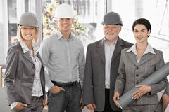 Confident team of architects. Wearing hardhat, holding plan, smiling at camera Royalty Free Stock Photography
