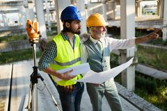Confident team of architects and engineers working together on construction site royalty free stock images