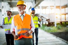 Confident team of architects and engineers working together on construction site royalty free stock photo