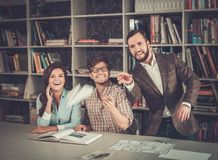 Confident team of engineers having fun in a architect  studio. Stock Image