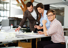 Confident team of engineers working together in a architect  studio. Royalty Free Stock Photos