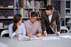 Confident team of engineers working together in a architect  studio. Confident team of engineers working together in a architect studio Royalty Free Stock Photo