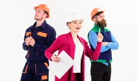 Confident team of workmen standing grouped in their dungarees. And hardhats smiling at camera isolated on white. Woman with documents has idea Stock Images