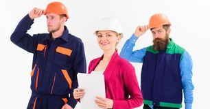 Confident team of workmen and woman standing. Grouped in their dungarees and hardhats smiling at camera isolated on white Stock Photo