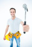 Confident technician holding hammer over white background Stock Photography