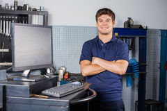 Confident Technician Standing Arms Crossed In Repair Shop. Portrait of confident male technician standing arms crossed by computer in auto repair shop Stock Photography