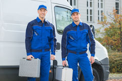 Confident Technicians Standing Against Truck Stock Photo