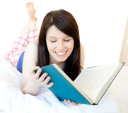 Confident teen girl studying lying on a bed Royalty Free Stock Images