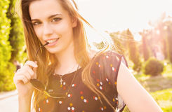 Confident teen girl in sunny outdoor setting. A confident and pretty brunette teen girl playfully holds the arm of her sunglasses to her mouth while looking stock images