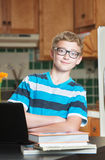 Confident teen with textbooks in kitchen Stock Photography