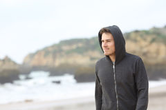 Confident teenager walking on the beach. Portrait of a confident teenager walking on the beach in a rainy day Royalty Free Stock Images