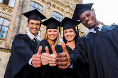 Confident in their successful future. Low angle view of four college graduates in graduation gowns standing close to each other and showing their thumbs up Royalty Free Stock Photos