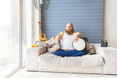 Confident thick guy playing musical instrument Stock Photos