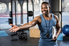 Confident trainer showing the gym to the camera stock images