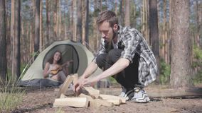Portrait handsome man in a plaid shirt prepares firewood to make a fire outdoors. The girl sits in a tent and plays the. Confident traveler puts firewood for the stock video footage