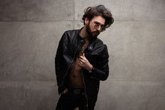 Confident trendy man in leather jacket. Young handsome man in black leather jacket on naked body and sunglasses posing confidently Royalty Free Stock Image