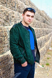 Confident trendy young guy against a stone wall Royalty Free Stock Images