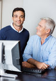 Confident Tutor With Senior Student In Computer Lab Stock Images