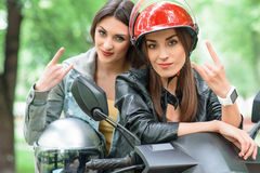 Confident two women traveling by scooter. Cool young girls are sitting on bike. They are showing rock and roll sign. Friends are looking at camera with Royalty Free Stock Image