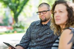 Confident University Student With Friend On Campus. Portrait of confident male university student sitting with female friend on campus Royalty Free Stock Photography