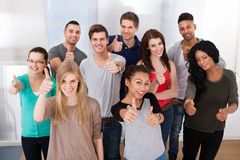 Confident university students gesturing thumbs up. Group portrait of confident multiethnic university students gesturing thumbs up in classroom Stock Image
