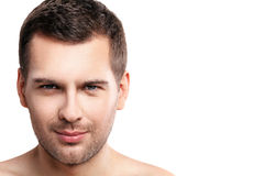 Confident unshaved guy is expressing his masculinity. Portrait of attractive young man looking at camera with confidence. He is standing with naked shoulders Royalty Free Stock Photos