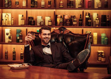 Confident upper class man with glass of beverage in gentlemen`s club Stock Photo