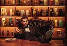 Confident upper class man with glass of beverage in gentlemen`s club Royalty Free Stock Photos