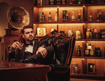 Confident upper class man with glass of beverage in gentlemen`s club Stock Photography