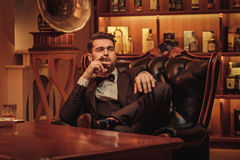 Confident upper class man with glass of beverage in gentlemen`s club Royalty Free Stock Photography