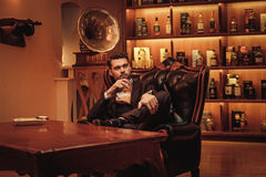 Confident upper class man with glass of beverage in gentlemen`s club Royalty Free Stock Images
