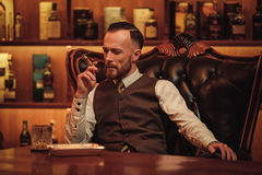 Confident upper class man smoking cigar in gentlemen`s club Stock Images