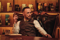 Confident upper class man smoking cigar in gentlemen`s club.  Royalty Free Stock Photography