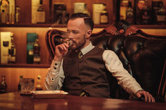 Confident upper class man smoking cigar in gentlemen`s club Stock Photos