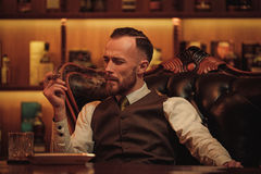 Confident upper class man smoking cigar in gentlemen`s club.  Royalty Free Stock Image