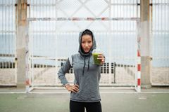 Urban fitness woman showing detox smoothie on workout rest stock images