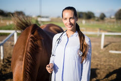 Confident vet standing by horse at barn Royalty Free Stock Photo
