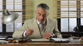 Confident vintage businessman working at desk stock video footage