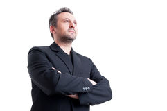 Confident and visionary business man. Posing from low angle looking up with arms crossed royalty free stock images