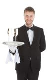 Confident waiter carrying champagne flutes on tray. Portrait of confident waiter carrying champagne flutes on tray over white background Stock Photos