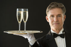 Confident Waiter Carrying Serving Tray With Champagne Flutes. Portrait of confident mature waiter in tuxedo carrying serving tray with champagne flutes against Royalty Free Stock Photos