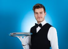 Confident waiter carrying tray Stock Photo