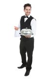 Confident waiter holding domed tray Stock Image
